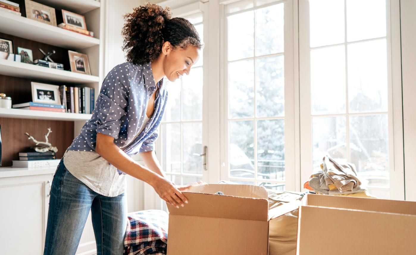 A woman unboxes her things in a new home after a recent move.