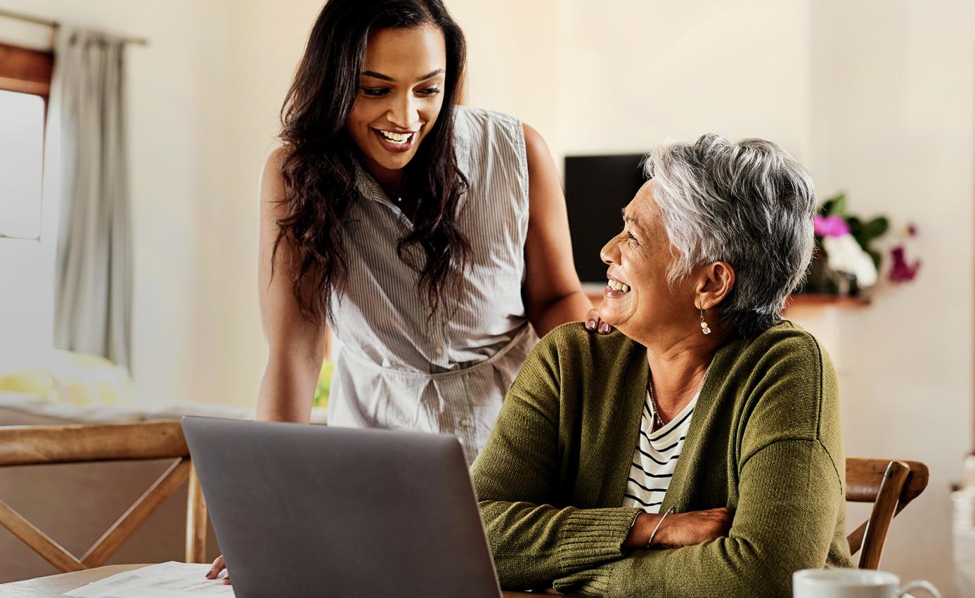 A senior woman laughs with her adult daughter as they review information on a laptop.