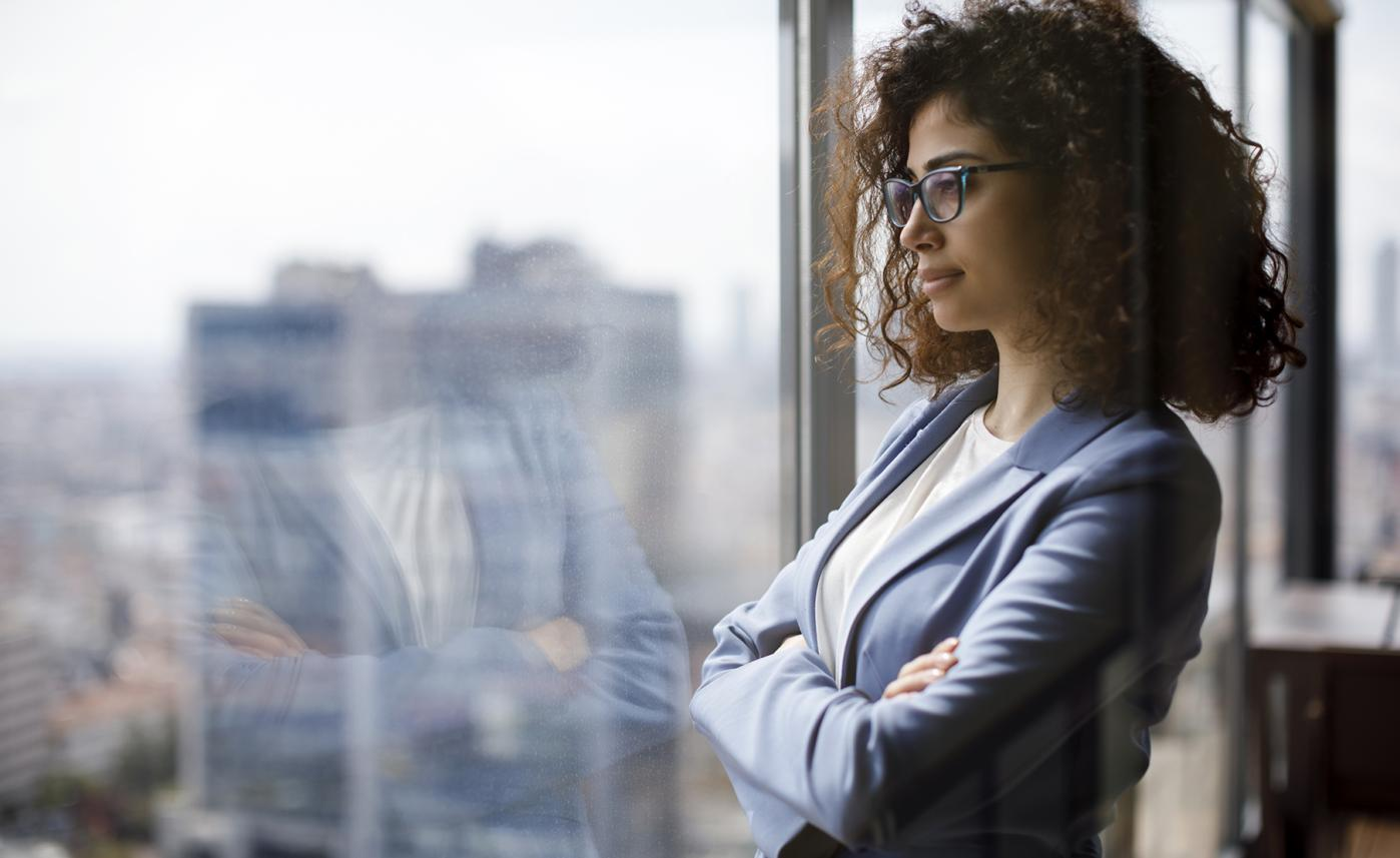 A woman confidently looks out a window on the first day of her new job.