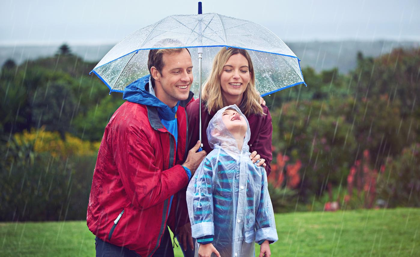 A young family stands together in the rain, smiling under an umbrella.