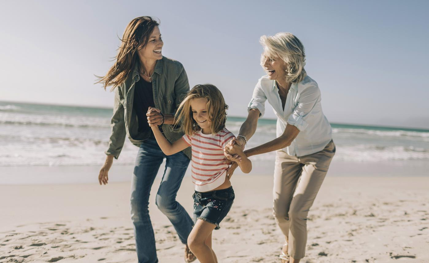 A retired woman laughs on the beach with her adult daughter and young granddaughter.