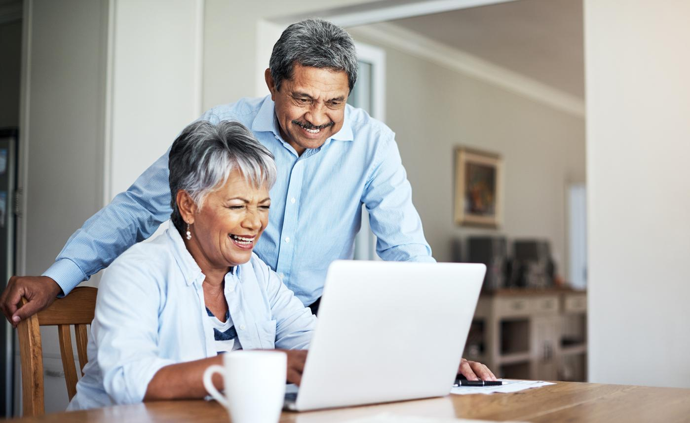 A retirement-aged couple reads information about trusts on their laptop at their kitchen table.