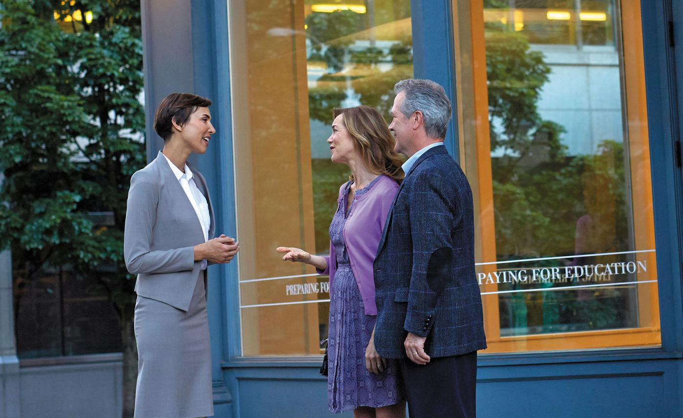 A financial advisor meets with two clients outside a blue building.