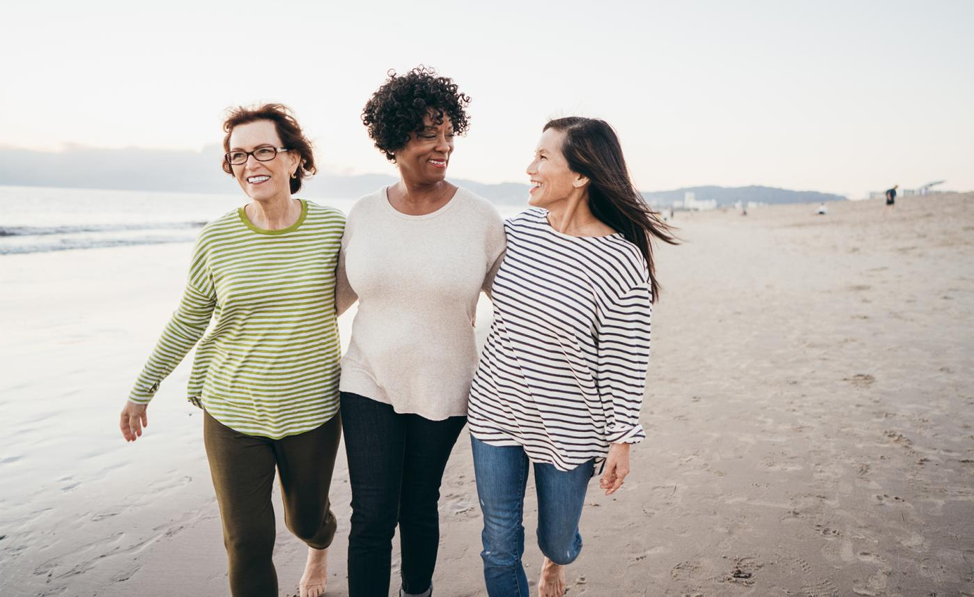 Three retirement-aged women walk together on a beach.