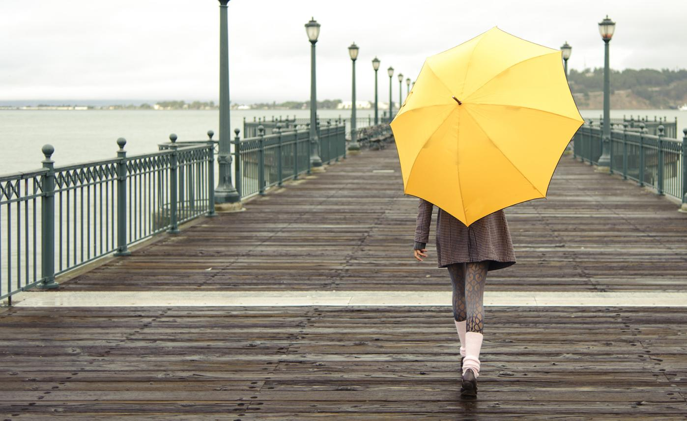 A young woman walks down a pier holding an umbrella on a rainy day.