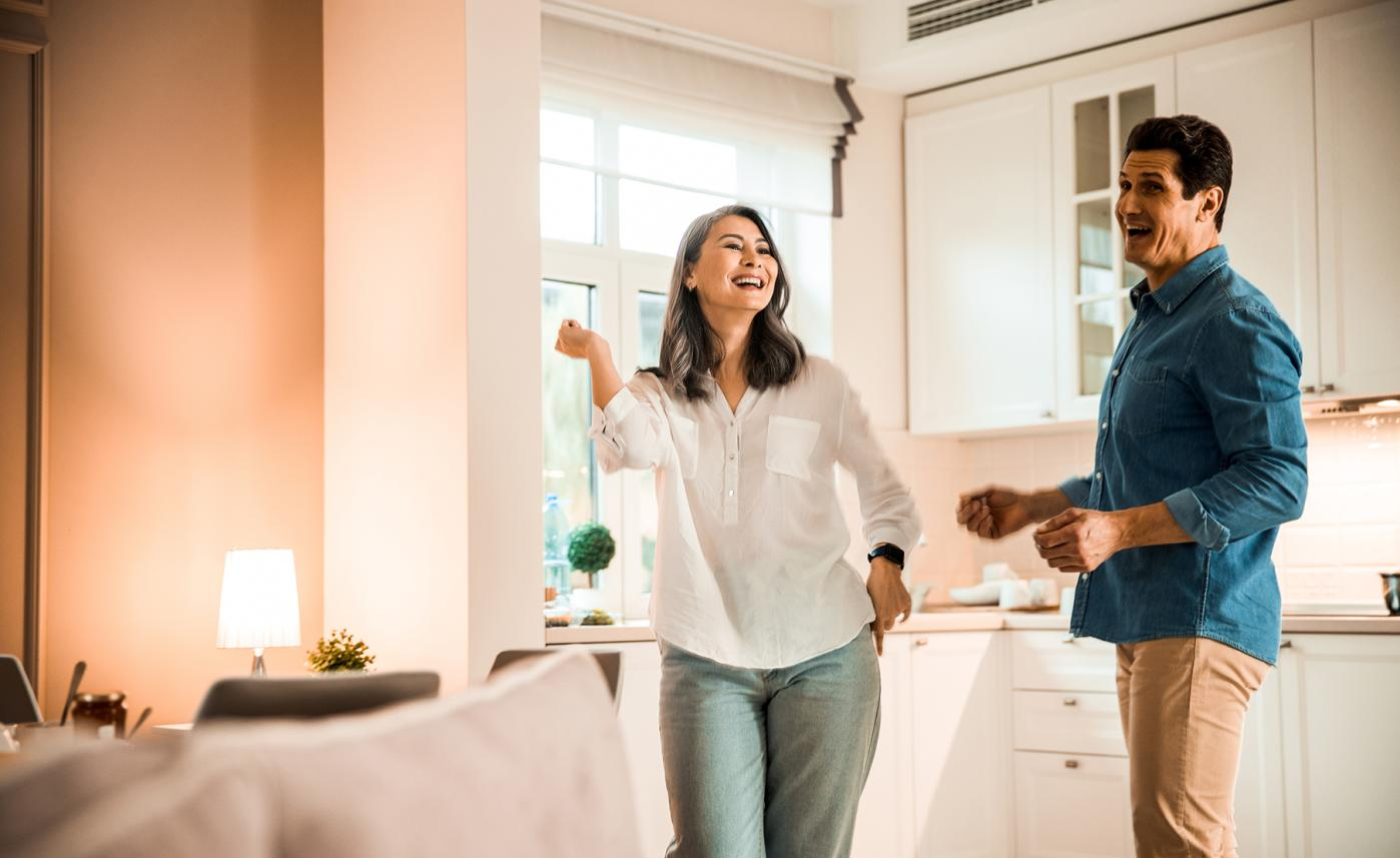 A retirement-aged couple enjoy time together in their kitchen.