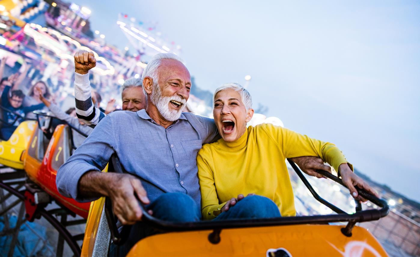 A retirement-aged couple having fun on a rollercoaster.