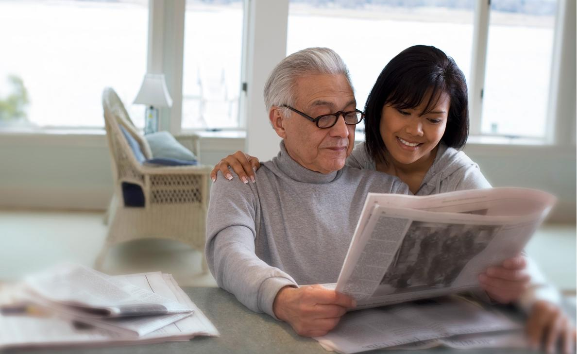 A woman reads a newspaper with her elderly father.