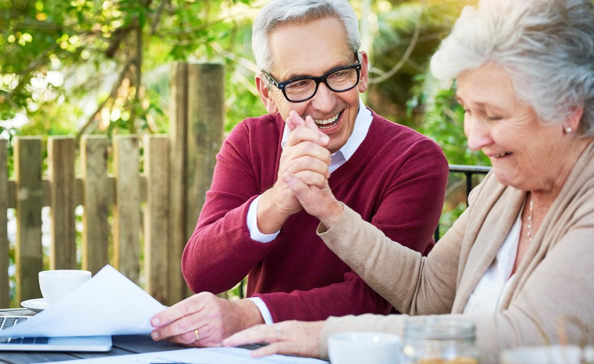 A retirement-aged couple smile and hold hands as they look at documents on their porch.