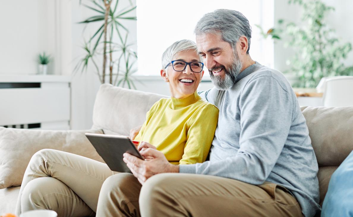 A retirement-aged couple smiles as they read from a tablet on the couch.