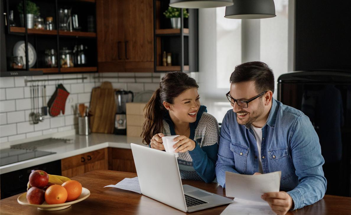 A young couple reviews retirement documents and their retirement account on their laptop in their kitchen.
