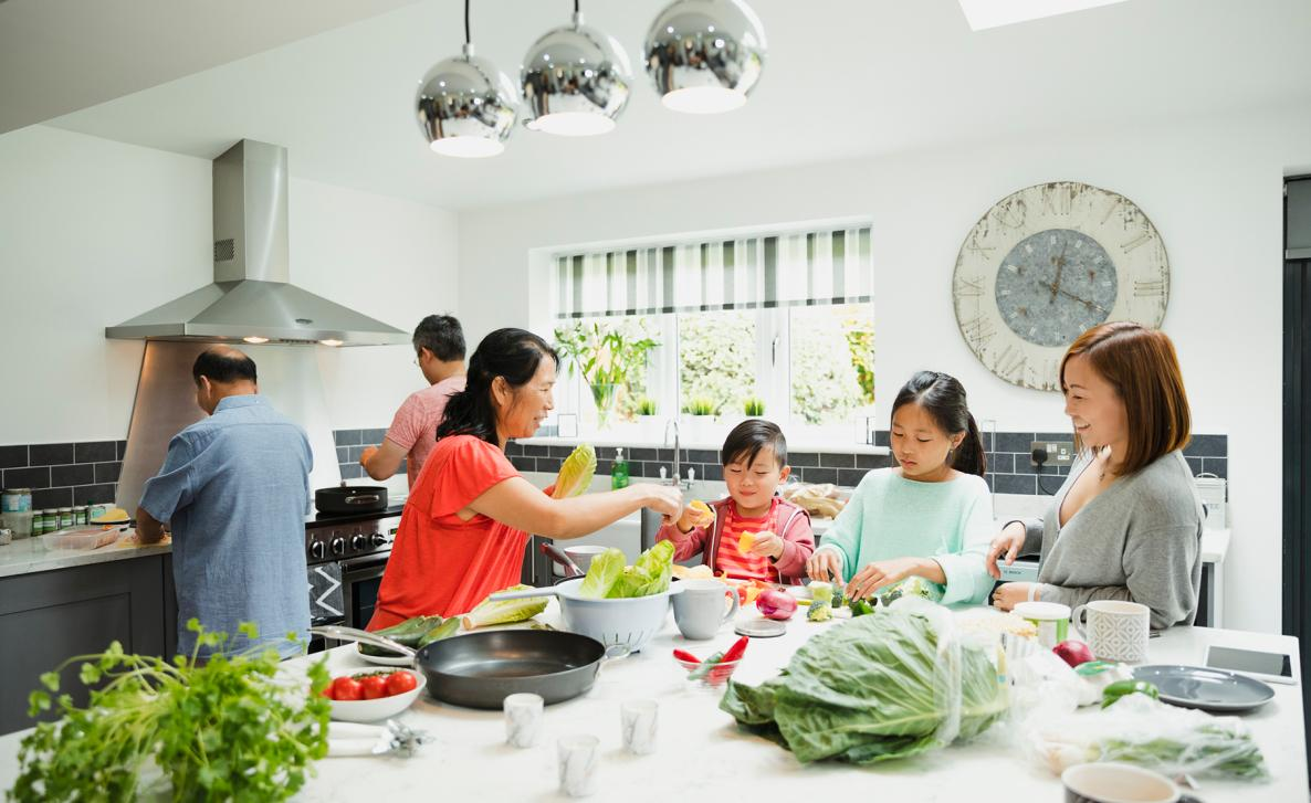 A big family prepares a dinner in their large kitchen.