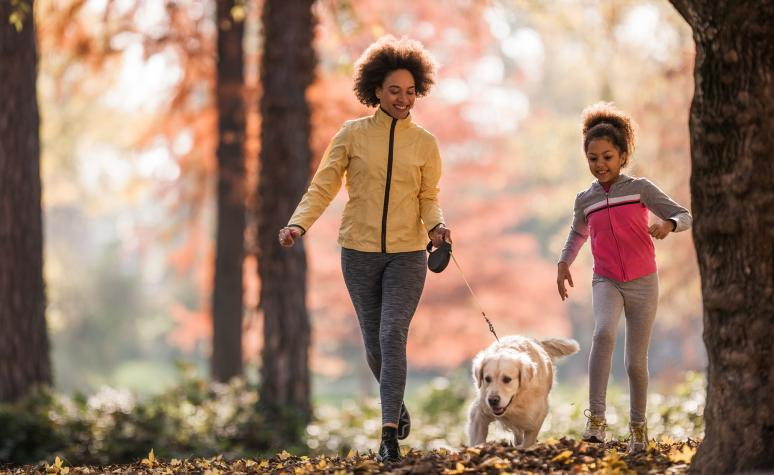 A mother and her daughter and dog walk down a hiking trail on a sunny autumn day.