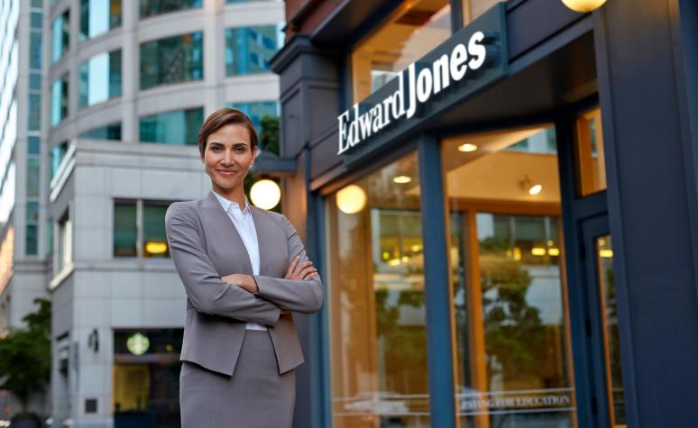 An Edward Jones associate stands outside the front of an Edward Jones branch.
