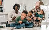 Young parents laugh with their three young boys in the kitchen.