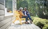 A senior couple smiles at each other on their porch on a sunny day.